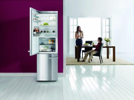 Kühlschrank vor lila Wand und mutter redet mit Sohn in WOhnzimmer